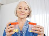 Senior woman looking at pill bottles in nursing home