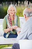 Smiling senior woman playing cards with man at nursing home