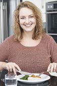 Woman On Diet Eating Healthy Meal In Kitchen