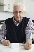 Senior Man Measuring Blood Pressure At Home