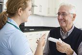 Nurse Helping Senior Man With Medication