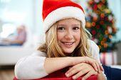 Portrait of cheerful girl in Santa cap looking at camera