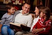 Portrait of happy family reading book on Christmas evening at home