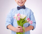 Little boy holding tulips for his mother