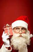 Curious Santa Claus holding red package by his ear