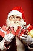 Santa Claus with several red giftboxes looking at camera