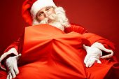 Portrait of happy Santa Claus embracing huge red sack with xmas presents
