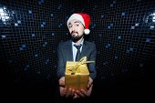 Young businessman in Santa cap holding giftbox