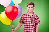 Smiling lad with balloons looking at camera in isolation