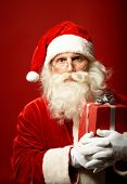 Surprised Santa Claus with red giftbox looking at camera