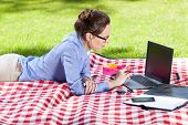 Pretty Woman Using Her Laptop In The Park