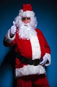 Santa Claus showing the thumbs up gesture and holdin one hand on his black belt.