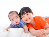 Cute little sister and baby laying on the bed fun