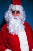 Portrait of Santa Claus looking at the camera against blue background.