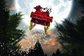 Santa flying his sleigh against full moon over forest