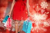 Woman standing with shopping bags against blurred snowflakes on planks