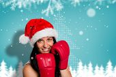 Woman wearing red boxing gloves against blurred fir tree background