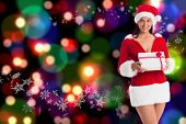 Woman smiling with christmas present against blurred lights