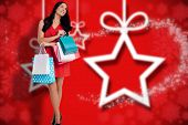 Woman standing with shopping bags against blurred christmas background