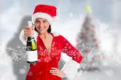 Woman holding a champagne bottle against blurry christmas tree in room