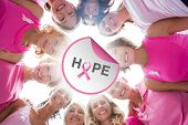 Cheerful women in circle wearing pink for breast cancer against breast cancer awareness message