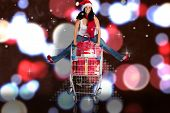Woman jumping with shopping trolley against blurred lights