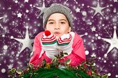 Wrapped up little girl blowing over hands against snowflake wallpaper pattern