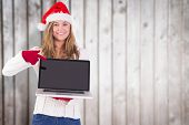 Festive blonde pointing to laptop against blurred wooden planks