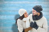 Young winter couple against blurred wooden planks