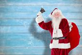 Santa claus ringing bell against blurred wooden planks