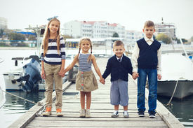 image of marines  - Group of 4 fashion kids wearing navy clothes in marine style posing in the sea port and holding hands - JPG