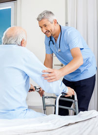 stock photo of zimmer frame  - Male caretaker assisting senior man to use walking frame in bedroom at nursing home - JPG