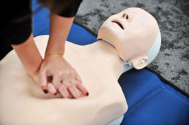 stock photo of resuscitation  - Hands of a woman are seen on a mannequin during an exercise of resuscitation  - JPG