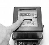 stock photo of electricity meter  - finger indicating the number on the meter of electricity - JPG