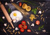 pic of pasta  - Raw pasta tomatoesmushrooms flour and eggs on black wooden table background top view - JPG
