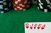 picture of flush  - hearts straight flush with poker chips on green table - JPG