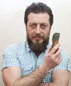 stock photo of beard  - Bearded man preparing to trim his beard with electric shaver - JPG