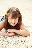 foto of children beach  - smiling cute little girl lying on the sand - JPG