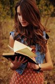 foto of auburn  - cute young woman with long auburn hair in the autumn forest reading a book - JPG