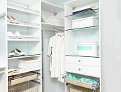 stock photo of shoe-box  - Detail of large walk in closet with wardrobe on hangers - JPG