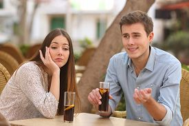 pic of seduce  - Man and woman dating in a restaurant terrace but she is boring while he speaks - JPG