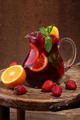 picture of jug  - Wine of Sangrija in a transparent jug on a wooden table with an orange and a strawberry - JPG