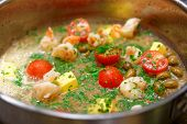 pic of shrimp  - Shrimps being cooked in broth and butter with tomatoes - JPG