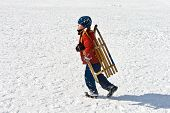 stock photo of snow-slide  - boy is carrying his sledge at the snow covered slope  - JPG