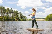 picture of ponds  - young woman fishing in pond during summer - JPG