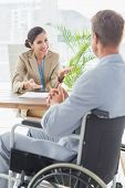 stock photo of interview  - Smiling businesswoman interviewing disabled candidate in an office - JPG