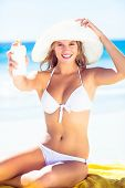 picture of sun-tanned  - Pretty blonde woman holding sun tan lotion at the beach - JPG