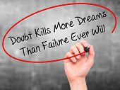 stock photo of kill  - Man Hand writing Doubt Kills More Dreams Than Failure Ever Will with black marker on visual screen - JPG