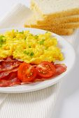 picture of scrambled eggs  - plate of scrambled eggs and fried bacon and slices of bread on white place mat - JPG