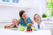 stock photo of cook eating  - Young mother and two children cooking in a kitchen - JPG